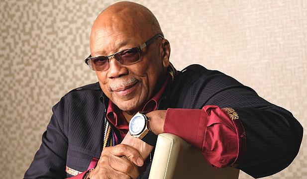 Quincy Jones sitting in a chair
